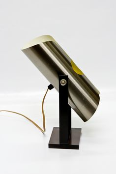 Tafellamp van het Nederlandse merk Raak design. De lamp kan scharnieren. De vierkante voet is van (doorzichtig licht bruinig / rookkwarts) plexiglas. Qua datering te plaatsen rond de jaren 60.