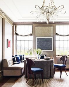 This elegant dining space combines nude bench seating, an animal print tablecloth, dark wood and navy chairs and a chandelier.