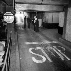 11/24/63 - Dallas Police study the spot where Jack Ruby shot and killed Lee Harvey Oswald hours before.