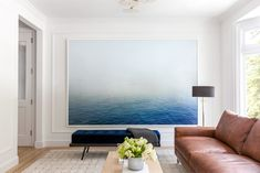 """I love playing with scale by using gallery or museum-sized art, which is totally unexpected in residential living,"" says Gibson. Here, in a client's living room, a 10' x 6' Peggy Wong photograph takes center stage alongside furniture and accents in neutral tones. ""The blue [of the photograph] is really the statement in this case,"" Gibson says 