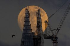 London Moon - New city architecture by moonlight. The Shard building in Southwark, designed by architect Renzo Piano, is complete. At 1,016 feet high, it is Europe's tallest inhabited building.