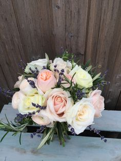 A hand tied spring bridal bouquet for a bride at Farnham Castle.  Flowers created by Eden Blooms Florist from David Austin 'Juliet' Rose, Sweet Avalanche, Hanoi Ranunculus, White 'O' Hara Rose, Dried Lavender, Avalanche Rose, Rosemary & Olive.