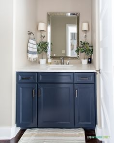 Guest bathroom with navy blue thermafoil cabinet, silver faucet, mini olive trees, and sconces. Painted Coffee Tables, Dream Bathrooms, White Ceramic Lamps, Block Printed Pillows, House Styles, Silver Faucet, Amazing Bathrooms, Spring Home, House Tours