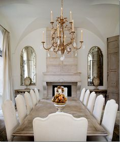 There is a beautiful antique stone mantel flanked by matching mirrors and consoles.