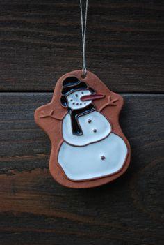Keramická+ozdoba+(sněhulák)+002+Ozdoba+z+keramické+hlíny+ve+tvaru+sněhuláka.+Ruční+výroba+dle+autorského+návrhu,+glazovaná.+Opatřeno+provázkem+k+zavěšení.+Dekorace+vhodná+na+vánoční+stromek,+adventní+věnec+či+štědrovečerní+stůl.+Jednotlivé+kusy+se+mohou+v+detailech+lišit.+Rozměry:+6+x+4+cm+barva:+hnědá+-+bílá+-+červená+-+černá+Každý+kus+je+ručně...