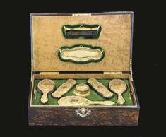 MARK OF PEAKE & CO., LONDON, 1899; 18K <BR> Comprising two hair brushes, two clothes brushes, a mirror, a comb, a pin tray and powder box and cover, each chased with rococo scrolls and flowers, on a matte ground, and centering a monogram <I>GJ</I>, <I>each marked on body</I>, in a fitted wood case with silver-gilt mounts, <I>marked George Betjemann & Sons, London, 1905</I><BR> The mirror 11 1/2 in. long; 15oz. weighable gold; the case 21 3/4 in. long (8)