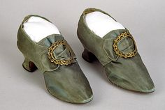 """Shoes, French or English, 1760-1775, green-gray satin weave silk; green-gray silk tape/binding; unbleached plain weave linen; leather; wood. (buckles not original). The tongues are backed with an ombre-striped silk. Writing on the inside of both is mostly illegible; possibly """"Perkins,"""" and """"c/r"""" and """"m/o"""". Soles did not see a lot of wear."""