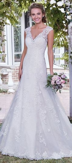 Beautiful lace appliqués waltz over the bodice, skirt, and hemline of this classic A-line wedding dress, with sheer lace comprising the illusion V over sweetheart neckline, cap-sleeves, and V-back. Finished with covered buttons over zipper closure.