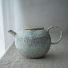 丸い形の陶器のポットです。 淡い青色の釉薬をまだらにかけています。 そそぎ口に茶漉しはついていないタイプです。   size 幅 11.5cm(取手からそそぎ口までの幅 17.7cm) 高さ10cm 口径 5.5cm  容量 約450cc 重さ 425g