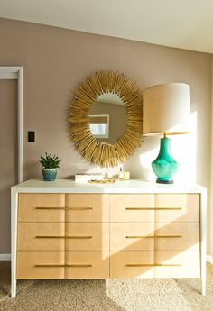 Vignette styled with emerald lamp and gold round mirror