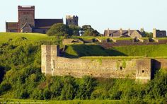 Field of Fire of Bell Battery at Sunrise, Dover Castle, Kent, England, UK. Skyline: Saxon St Mary-in-Castro Church, Roman Pharos, Victorian Garrison School, Norman Colton Gateway. Below school are v-shaped openings of artillery cannon positions. Bottom: Avranches Tower, South Watchtower, Eastern Outer Curtain Wall. Listed Building, English Heritage site, Scheduled Ancient Monument. Tourism and Travel. Medieval, Napoleonic Wars History. More information at…