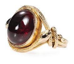 Victorian Garnet Snake Ring with garnet oval cabochon of an approximate 5.70 carats has been foiled beneath and set closed back in a 15k yellow gold mount with patterning all around the surface. Wrapped in an embrace about the setting are two sensual snakes. Each snake head overlaps the body of its mate and tails entwine about the shoulders of the shank. Engraved details such as eyes and skin texture accent the fineness of the double shanked ring.    Date: Circa 1890.