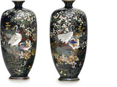 A pair of small cloisonné enamel vases Meiji period (late 19th century) Worked in silver wire and colored enamels on a black ground with various birds among blossoming prunus and other flowers, the foot decorated with a stiff leaf band and the neck with a band of hanging jeweled garlands, silvered mounts