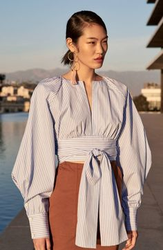 Cut from fine shirting-striped poplin from Italy, this romantic blouse captivates with a deep keyhole slit in front and flowy back panel showing a tease of skin. Long, figure-sculpting ties wrapping the waist heighten the drama and multiply the styling options.