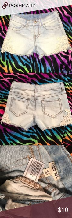 """Crochet side stretch jean shorts XS/5 Cherokee Girls Cherokee stretch jean shorts with crochet hem detail. Size is XS, but comparable to girls 5 when I checked against the other pairs I am listing. Super light stone wash with dark tan stitching.  These are so adorable and perfect for the little girl that wants to dress like her big sister. Adjustable waist. Zip fly and snap close. Excellent preowned condition. Material: 72% cotton, 27% polyester, 1% spandex  Waist measures approximately 22""""…"""