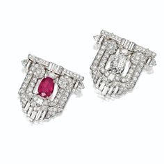 PAIR OF ART DECO DIAMOND AND RUBY CLIPS, CIRCA 1930. Designed as geometrical arches, one set in the center with a pear-shaped diamond weighing approximately 1.15 carats, the other with an oval ruby weighing approximately 2.00 carats, completed by 20 baguette, 8 fancy-shaped and 70 old European-cut diamonds weighing a total of approximately 4.40 carats, mounted in platinum.