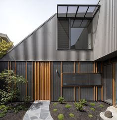 Although the property looks like a one-story home from the street, its second level is more noticeable from the enclosed courtyard. Timber battens were used to add interest to the exterior.