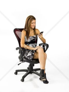 smiling at phone - A teen girl, sitting in a chair, smiles to her phone