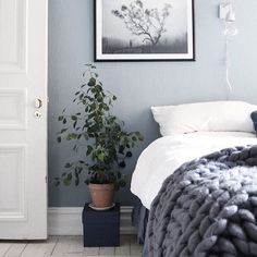 Cosy blue bedroom with chunky knit blanket and white bedsheets, and a framed poster from Printler, the marketplace for photo art. Interior design by Cream and navy.