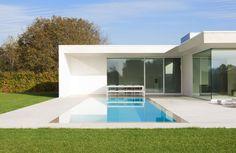 Skimmer zwembad met strakke witte poolhouse betonnen zwembad