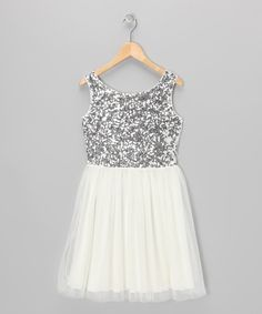 This elegant dress has plenty of frills to satisfy the masses. A dainty tulle overlay punctuates the skirt, while a sequin-kissed bodice makes up the fashion focal point.Shell: 100% polyesterLining: 100% cottonHand wash; hang dryImported