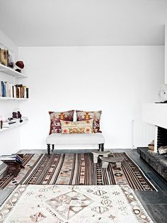 A bit too minimalist for me, but I love the tones on the rugs and pillows & the patterns. Also the shelving is great.