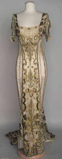 Circa 1908 one-piece evening gown: short sleeves, long narrow train, all over embroidery and beading w/ribbon, bronze thread, gold beads, silver bugle beads, rhinestones, pearls, and white silk ribbon.