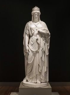 Harriet Hosmer portrayed Zenobia, a 3rd-century Queen of Palmyra (near present day Syria), as a prisoner of the Roman Empire. Although defeated, the queen possesses a regal bearing & wears elaborate court dress, complete with diadem. In the legend, when Emperor Aurelian saw Zenobia's dignity & beauty while shackled, he freed her. Hosmer conveyed the exact qualities that led to Zenobia's pardon. Hosmer carved Zenobia in 1859 & exhibited it in 1862 at the Great London Exposition
