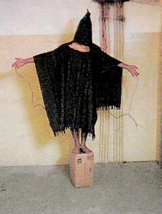 Fotos wie dieses erschütterten 2004 die Welt: Ein Häftling wird in Abu Ghuraib von seinen amerikanischen Wärtern gezwungen, stundenlang auf einer Kiste zu stehen, die Hände in der Luft. An seinen Fingern sind Kabel befestigt. Seine Wärter warnten ihn, wenn er die Arme sinken ließe, würde er eine Bombe zünden, die ihn tötet. Der Häftling kann wegen der Kapuze nicht sehen, dass die Kabel im Nichts verlaufen.