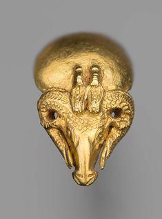 Gold ram's head earring with two uraeii and the sun disc, rosette on the back. Nubian Napatan Period 550–500 B.C. Findspot: Meroe, Nubia, Sudan