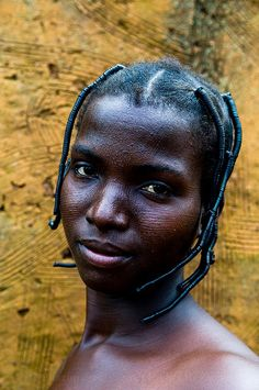 Portrait of a young Somba (Betammaribe ) woman taken in her village.Both Somba men and woman decorate their faces and bodies with linear scars. Interesting to see her small house decorated with the same form of art. Photo taken in the Atakora region in North Benin