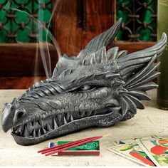 Fragrant, incense smoke rises from the vented nostrils of this absolutely awesome fire-breathing dragon sculpture, lending mystery to any Medieval decor. Raise the upper jaw of this fierce, Gothic skull statue to stash your extra sticks.dragon head m Dragon Head, Dragon Art, Fantasy Dragon, Dragon Incense Burner, Burning Incense, Fire Breathing Dragon, Incense Sticks, Grey Stone, Decorative Objects