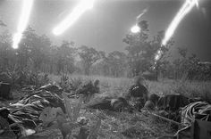 Flares from planes light a field covered with the dead and wounded of the ambushed battalion of the U.S. 1st Cavalry Division in the Ia Drang Valley, Vietnam, on November 18, 1965, during a fierce battle that had been raging for days. Units of the division were battling to hold their lines against what was estimated to be a regiment of North Vietnamese soldiers. Bodies of the slain soldiers were carried to this clearing with their gear to await evacuation by helicopter. (Rick Merron/AP)…