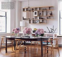 Dining room + library: Floating shelves + Wegner wishbone chairs, from Elle Decor    In Lisa Pomerantz's Chelsea apartment, the dining room doubles as a library. Berkeley extension table by Scott Jordan furniture. Wishbone chairs by Hans J. Wegner. Metamorphosis Pendant 3-M light by Collura & Co.    Interior design by Peter Pawlak. Photo by Joshua McHugh, Elle Decor, Jan/Feb 2008.