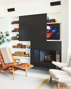 In a library of a New York loft, an Arne Vodder chaise longue, a Hans Wegner armchair upholstered in a Rogers & Goffigon fabric, and a custom-made plaid rug; the fireplace surround and sliding panel are of blackened metal, and the television is by Samsung.
