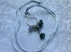 Green Cluster Necklace Handmade silver plated swirl with a cluster of green glass beads on a satiny green cord.