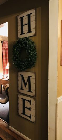 Home sign with boxwood wreath.