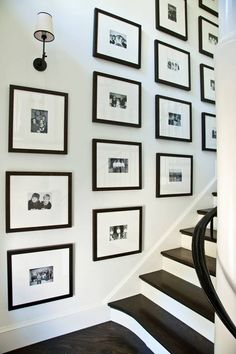 An AWESOME way to display family pics orderly.  This is done with family holiday cards... reprinted black and white and framed in black frames, so they make both a graphic statement and also tell a fun story.