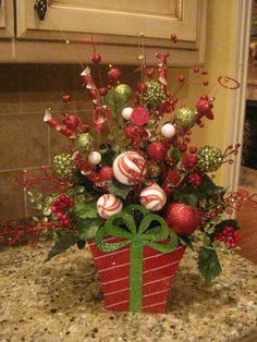 This arrangement is fun and whimsical! It is full of Christmas ornaments, glittery sticks and holly in a metal present container. It would look