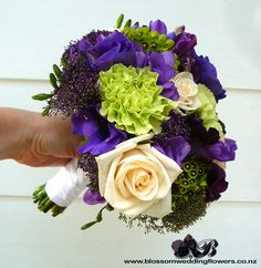 Posy style bridesmaids using cream roses, purple lisianthus, anemones, freesia, sweet peas, trachelium, tulips, and green, carnations and blupernum, bound in white satin and pinned with pearls