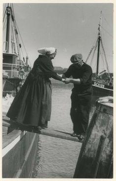Tweede haven, een behulpzame visser helpt zijn echtgenote over de loopplank. ca 1949 WF van Heemskerck-Düker #ZuidHolland #Scheveningen