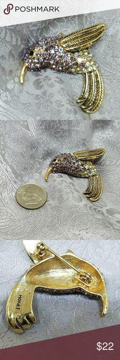 Vintage Monet Hummingbird Pin Cute little hummingbird decorated with lavender amd green crystals and gold tone. From jewelry designer Monet this little bird is in excellent condition with no chips cracks or missing stones. Monet Jewelry Brooches