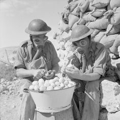 Soldiers wearing gas masks while peeling onions at Tobruk, 15 October 1941.