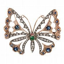 "RUSSIAN GOLD AND JEWEL ENCRUSTED BROOCH IN THE MANNER OF CARL FABERGE; butterfly-form set with 57 diamonds, 16 sapphires, two rubies, and an emerald. Stamped with ""56"" for 14K fineness and pseudo mark for Faberge / SOLD  $1,840"