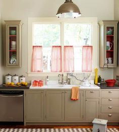 A nice variety of muted neutrals -- including chalky white on the walls and warm taupe on cabinets -- make this kitchen a place where you can imagine whipping up a warm meal. Rich orange interiors peek out from behind the upper cabinets' glass, and the curtains show off a similar shade but in an airy sheer fabric.