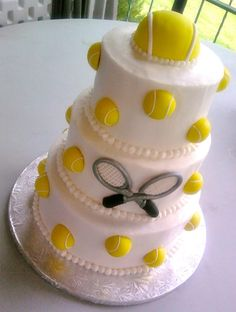 This 3 tier wedding cake has a smooth base on all tiers with a fondant tennis ball topper and fondant tennis balls on all tiers and criss crossing tennis rackets on the front of the middle tier. There is a piped border on all tiers. This cake serves 78