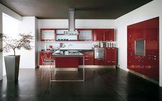 Esta es la cocina.  Es una cocina muy espaciosa donde prevalen el rojo y el negro. En el centro hay una mesa roja y algunas sillas donde comemos todas juntas. El frigorífico y los cajones donde hay los cubiertos se encuentran el la pared; el lavavajillas, los fogones y el fregadero se sitúan en el otro lado.  A la izquierda hay una maceta con una planta.