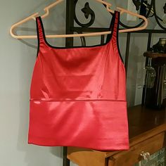 Red Top Silky red top with black trim and back straps.  Would call it a midriff tamer top :-) Has built in elastic band in the lower half under the breast.  Never been worn but do not have tags. Rago Tops Camisoles