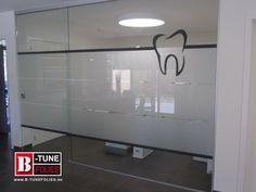Glazen wandpaneel bij een tandartspraktijk, voorzien van matte raamfolie en een belettering gesneden folie,
