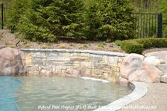 Gunite sun shelf on this hybrid swimming pool features a raised retaining wall as the edge of the pool, anchored by custom hand carved concrete boulders.